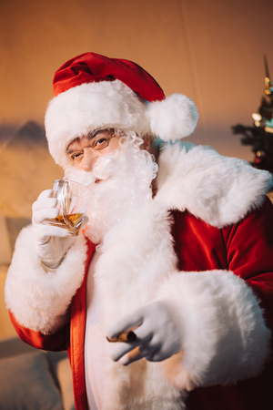 santa claus with glass of whiskey and cigar