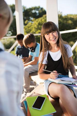 本で勉強して笑みを浮かべてティーンエイ ジャー 写真素材