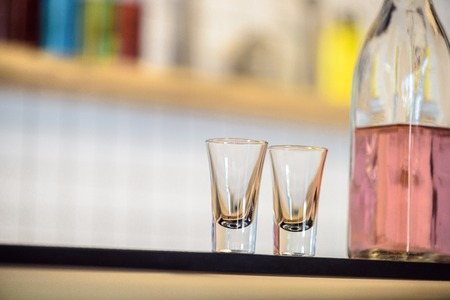 close-up view of empty glasses and bottle with alcoholic beverage on bar counter Foto de archivo