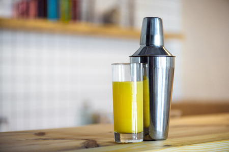 close-up view of glass with fresh juice and shaker on wooden bar counter Stock Photo