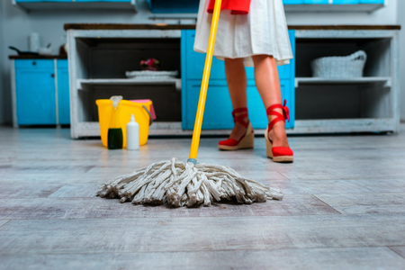 low section of housewife mopping floor in kitchen Фото со стока