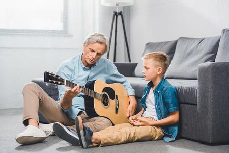 Großvater und Enkel spielen auf der Gitarre Standard-Bild - 86378579
