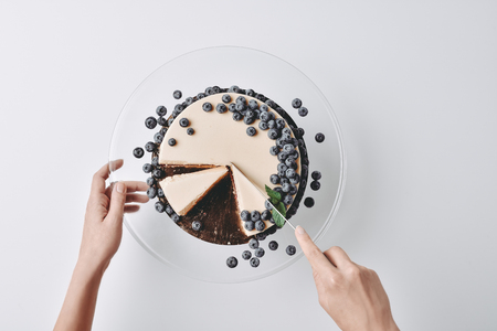 woman slicing cheesecake with blueberries
