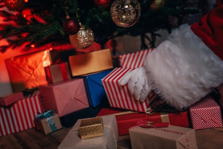 santa with gifts under christmas tree
