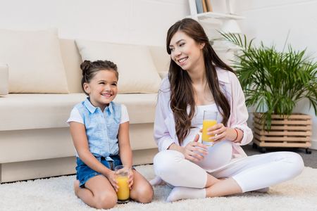 Pregnant woman and daughter with glasses of juice