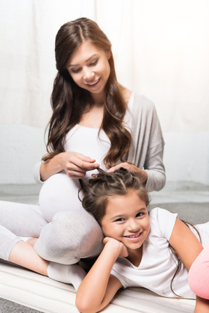 Pregnant woman with daughter sitting on rug Stock Photo