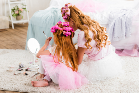back view of mother and daughter with curlers on heads doing makeup together