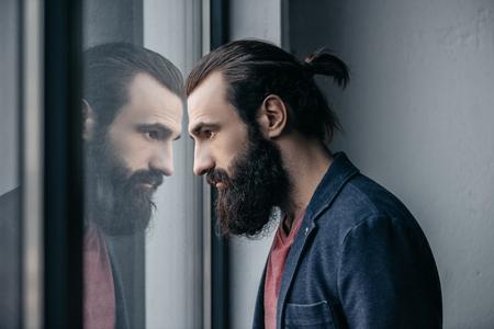 Mann, der Reflexion im Glas betrachtet