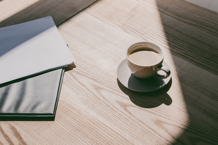cup of coffee and notebooks on table Stok Fotoğraf