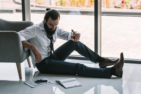drunk businessman sitting on floor Banco de Imagens