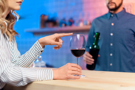 bartender pouring wine to woman Stock Photo