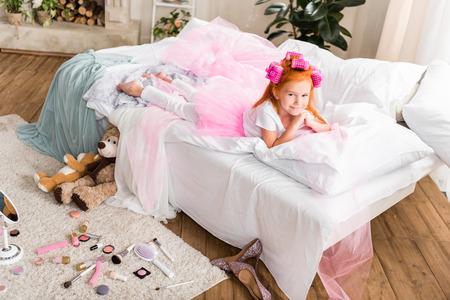 ベッドの上で休んでいるカーラーを持つ小さな女の子