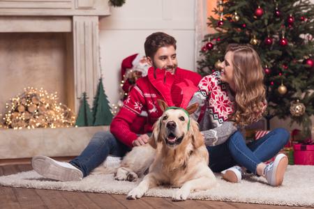 couple with dog at christmastime 版權商用圖片