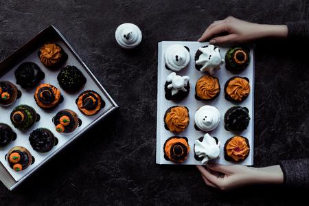 hands holding halloween cupcakes Stock Photo