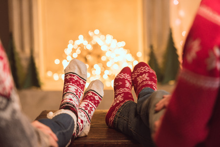 couple in knitted socks near fireplace Stock Photo