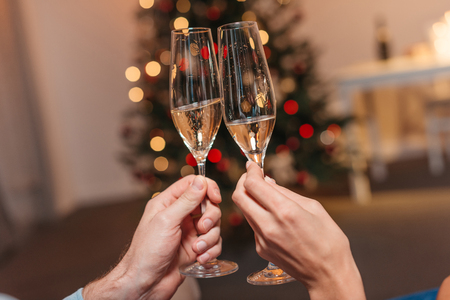 close-up partial view of couple clinking glasses with champagne at christmas Stock Photo