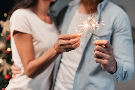 cropped shot of young couple holding sparklers at new year party