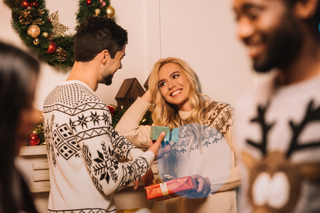 multiethnic couple exchanging christmas gifts Stock Photo
