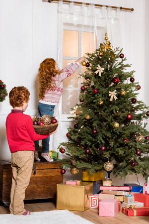 siblings decorating christmas tree