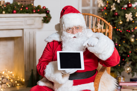 santa claus pointing at tablet