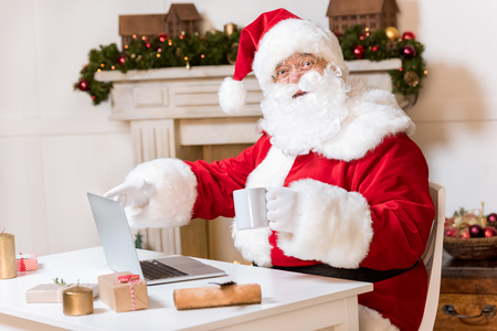 santa claus with laptop at home Stock Photo