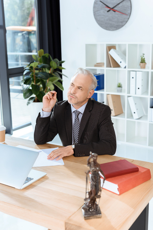 mature lawyer sitting at workplace
