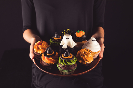 cropped shot of person holding plate with homemade spooky halloween cupcakes