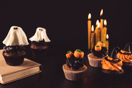 close-up view of sweet homemade halloween cupcakes and burning candles Stock Photo