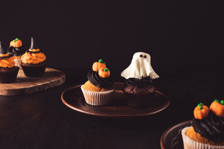 close-up view of delicious decorative halloween cupcakes on black Stock Photo