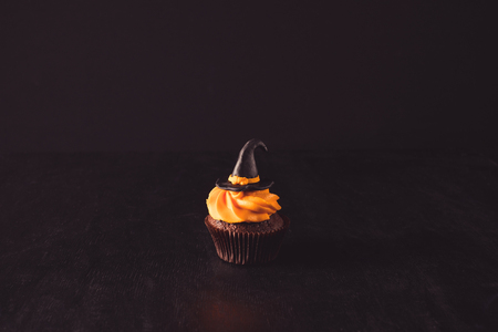 close-up view of delicious decorative halloween cupcake with witch hat on black Stock Photo