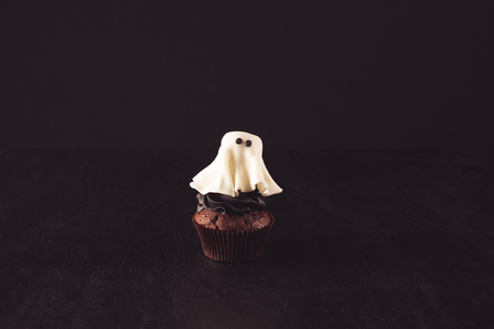 close-up view of spooky tasty halloween ghost cupcake on black
