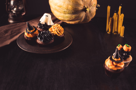 close-up view of decorative delicious halloween cupcakes, ripe pumpkin and candles