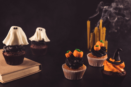 Close-up vista de doces decorativos cupcakes de halloween, livro e velas Foto de archivo - 87846780
