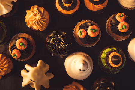 top view of traditional tasty halloween cupcakes on black