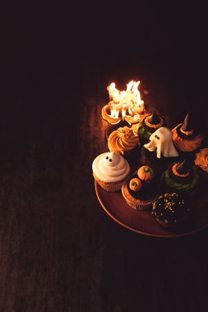 close-up view of delicious halloween cupcakes and burning candles in black