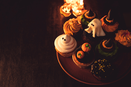 close-up view of traditional halloween cupcakes and burning candles in black