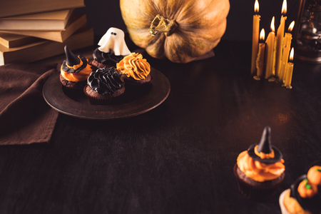close-up view of traditional delicious halloween cupcakes, books, pumpkin and burning candles