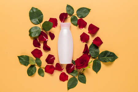 body lotion in bottle in floral frame, isolated on orange