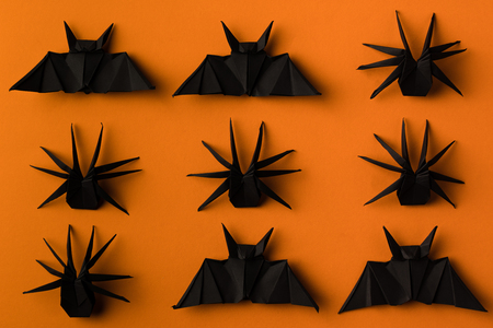 black origami spiders and bats for halloween, isolated on orange