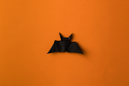 black halloween origami bat, isolated on orange