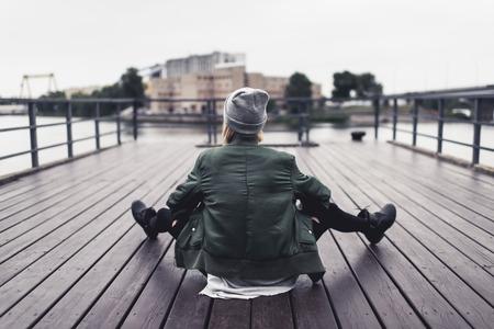 木製の桟橋に座っているスタイリッシュな女性の背面図