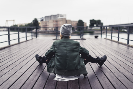 back view of stylish woman sitting on wooden pier