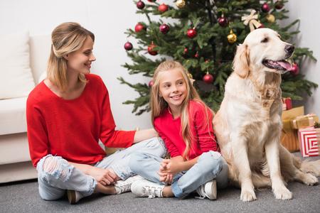 moeder, dochter en hond op kerstboom Stockfoto
