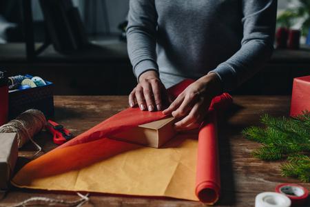 woman wrapping book as christmas gift Stok Fotoğraf