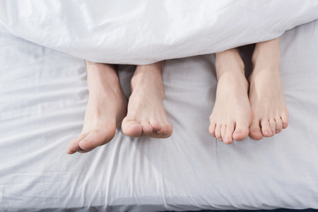 feet of couple stretching out of blanket Stockfoto