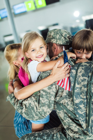 family hugging father at airport Stock Photo