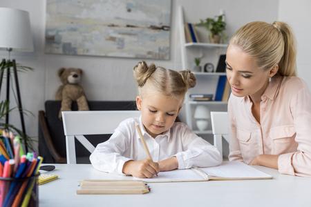 kind tekenen met moeder Stockfoto