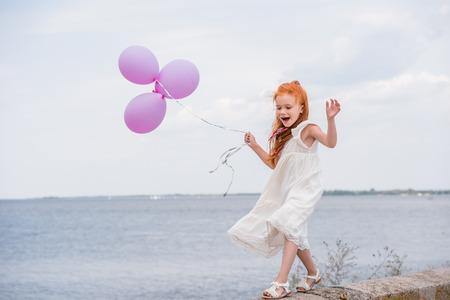 kind met ballonnen op kade