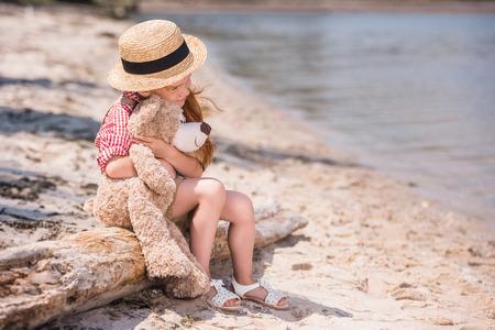 child with teddy bear at seashore Stock Photo