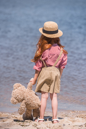 child with teddy bear at seashore Stock Photo - 88528228